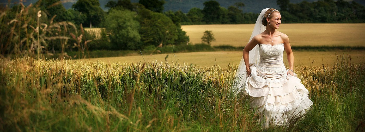 A bride walking in a field by Yourk wedding photographer Gary Simpson