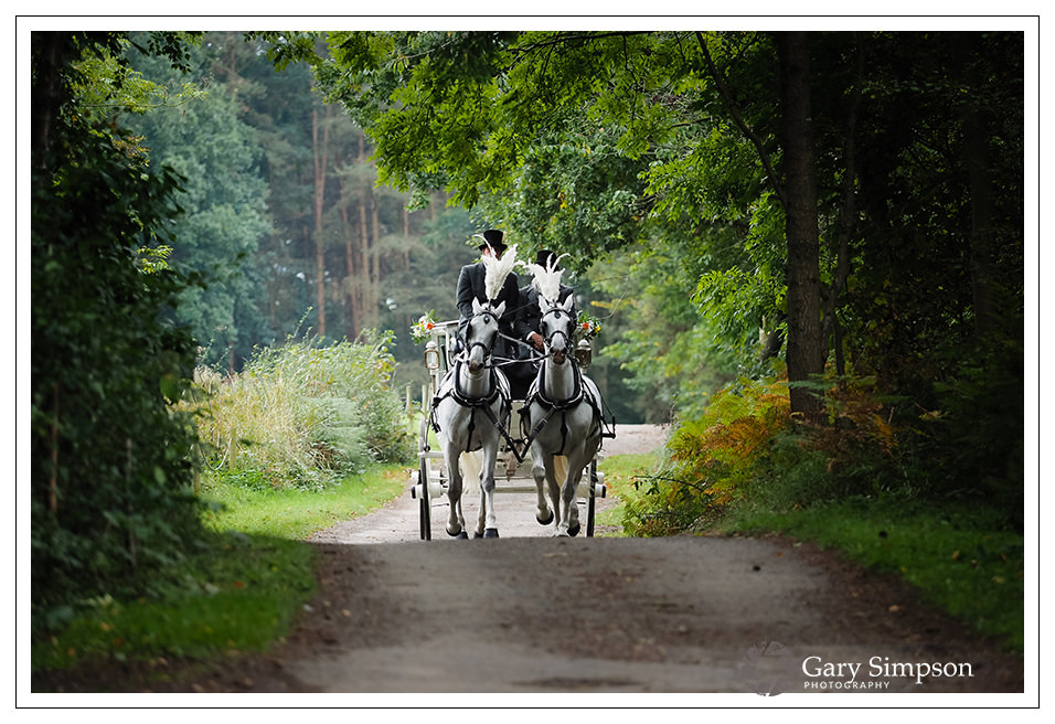 bride arriving in a horse drawn carriage at camp katur in north yorkshire