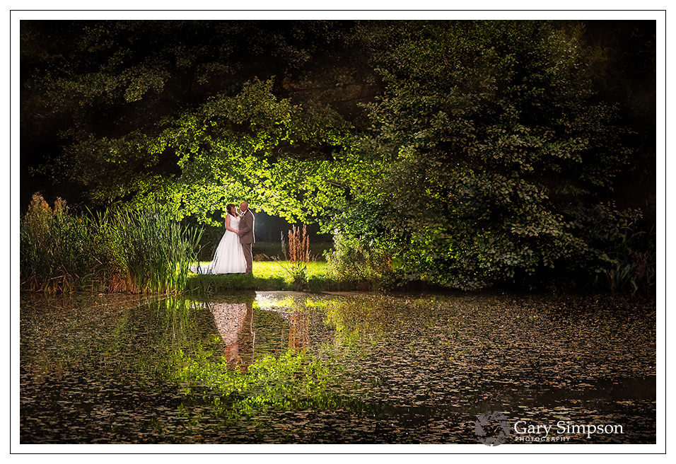 bride & groom portrait over looking the lake in the woods of camp katur in north yorkshire