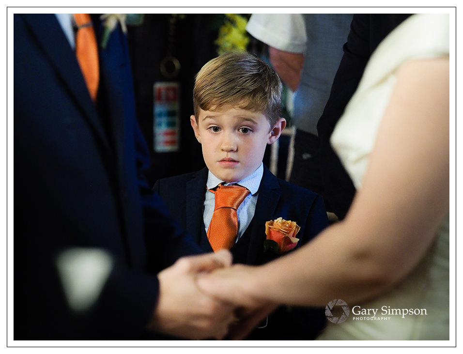 page boy at crossbutts stables during the wedding ceremony
