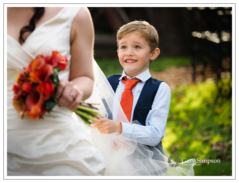 page boy helping the bride with her dress