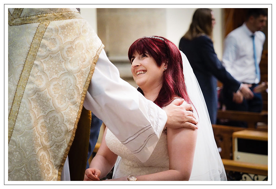 The bride shares a joke with the priest at St Wilfred's church