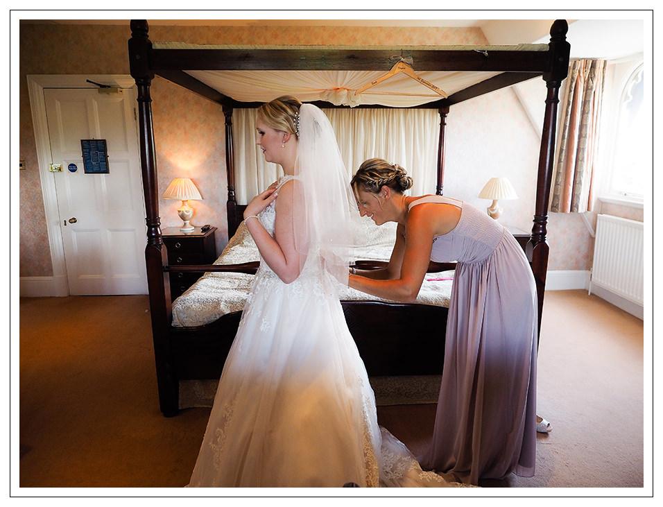 bridesmaid fastening the brides dress