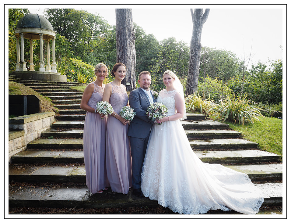 bride and groom portrait with the bridesmaids on the gardens of rushpool hall