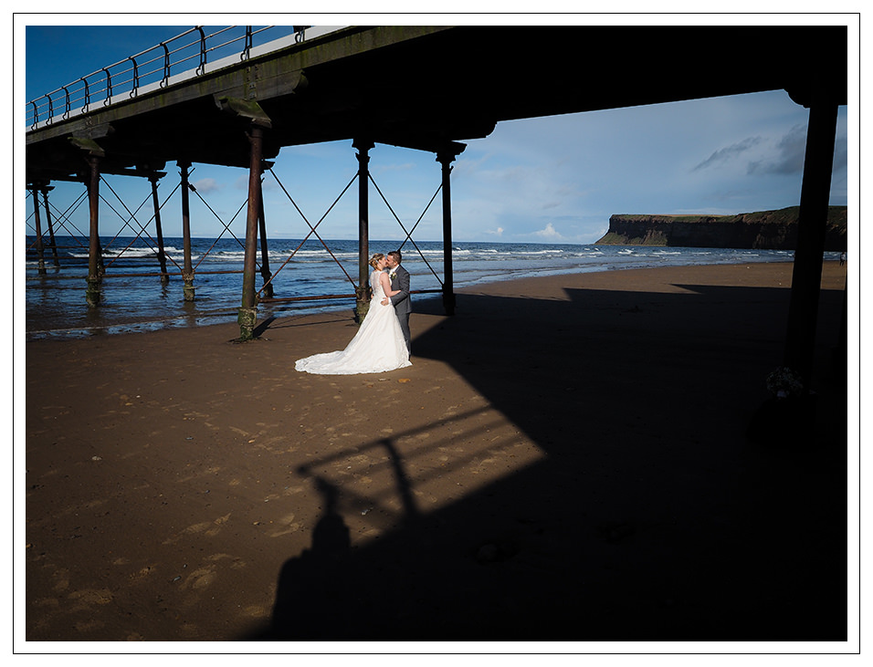 on the beach at saltburn for a bride and groom portrait