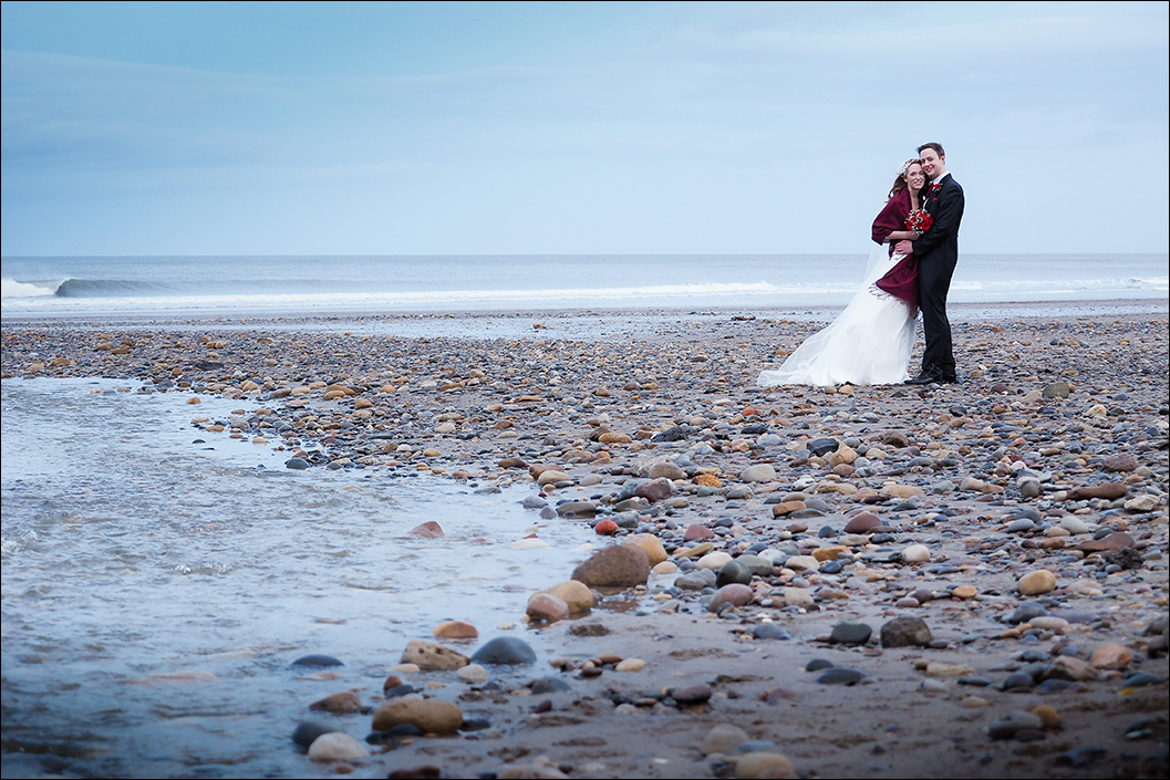 portrait of the bride & groom on sandsend beach after their wedding ceremony at raithwaite hall