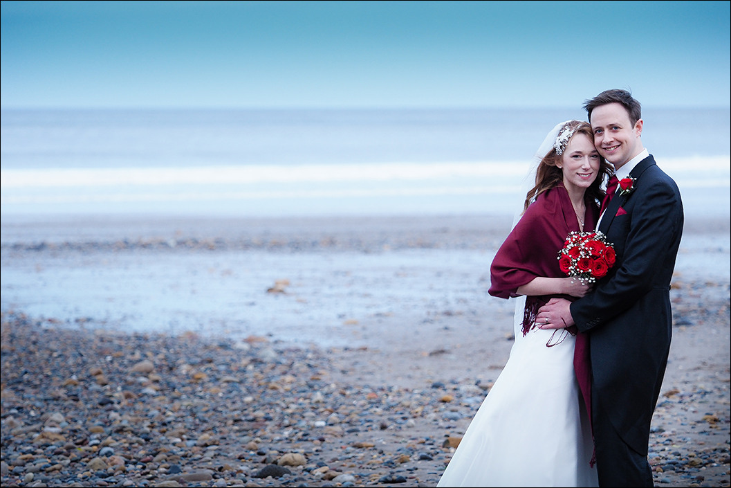 bride and groom portrait on sandsend beach on a cold january day