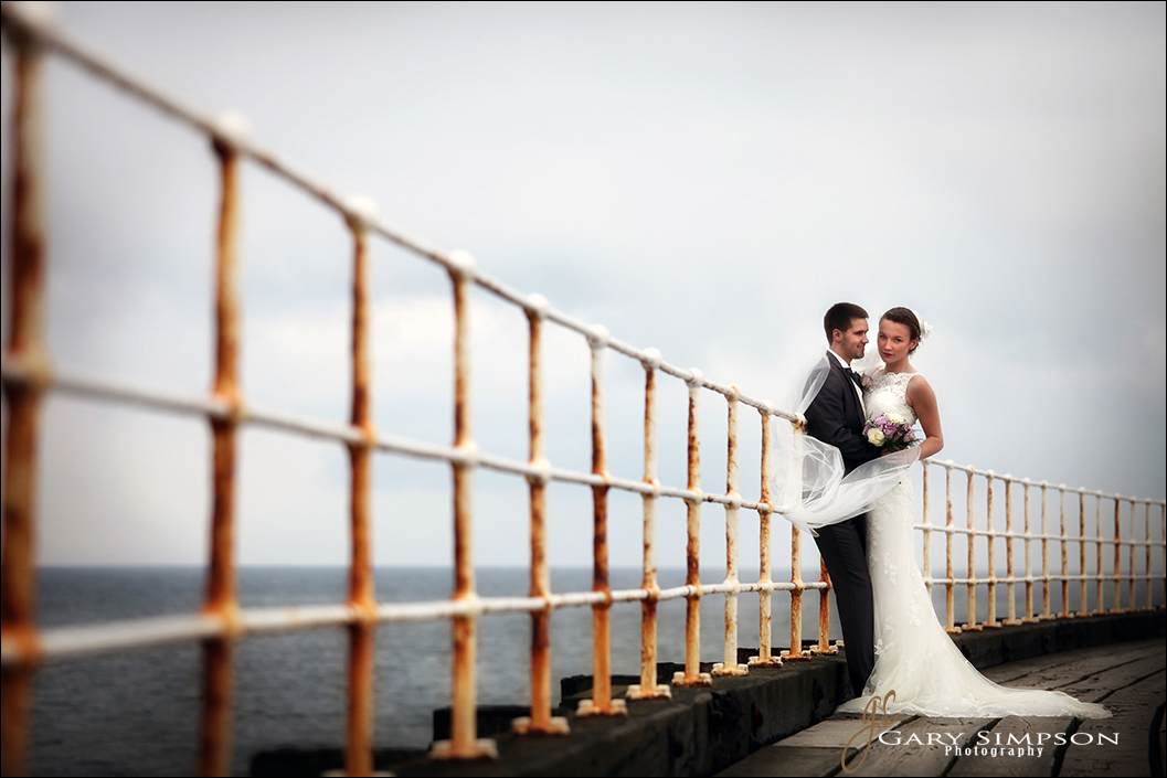 bride and groom on whibty pier