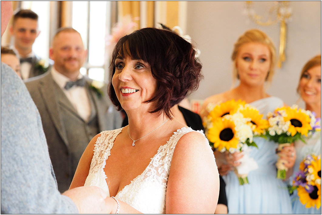 a smiling bride at oulton hall for the start of the wedding ceremony
