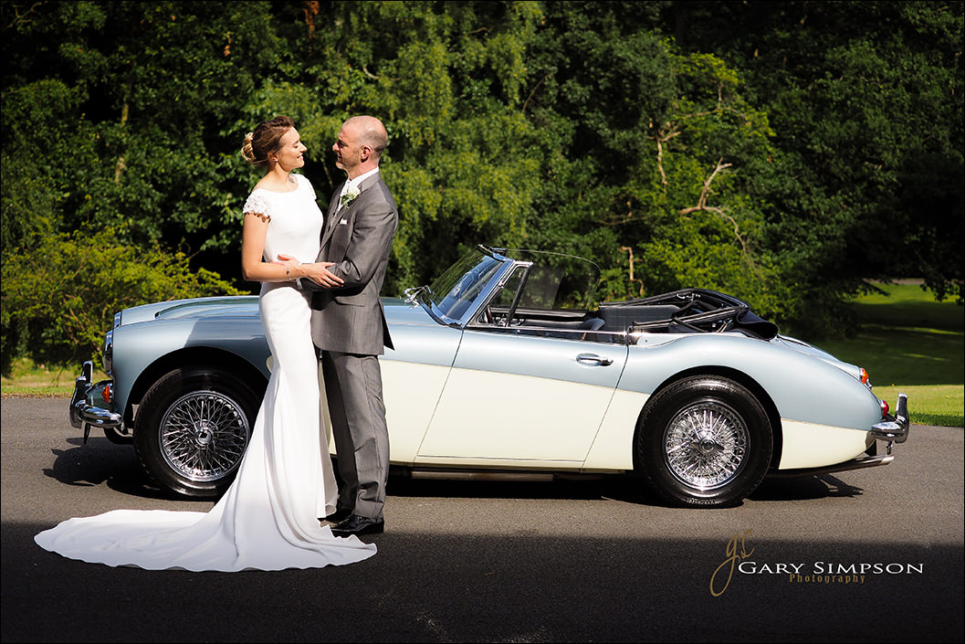 bride and groom with a austin healey at wrea hotel