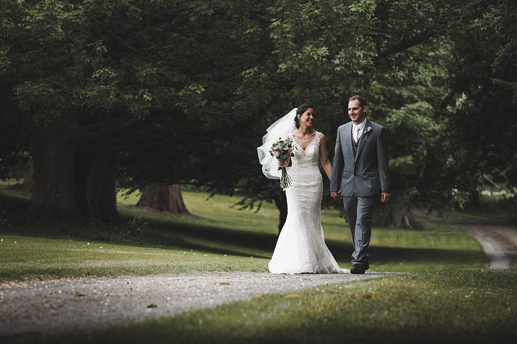 gary simpson photography. bride and groom walking in the gardens of howsham hall