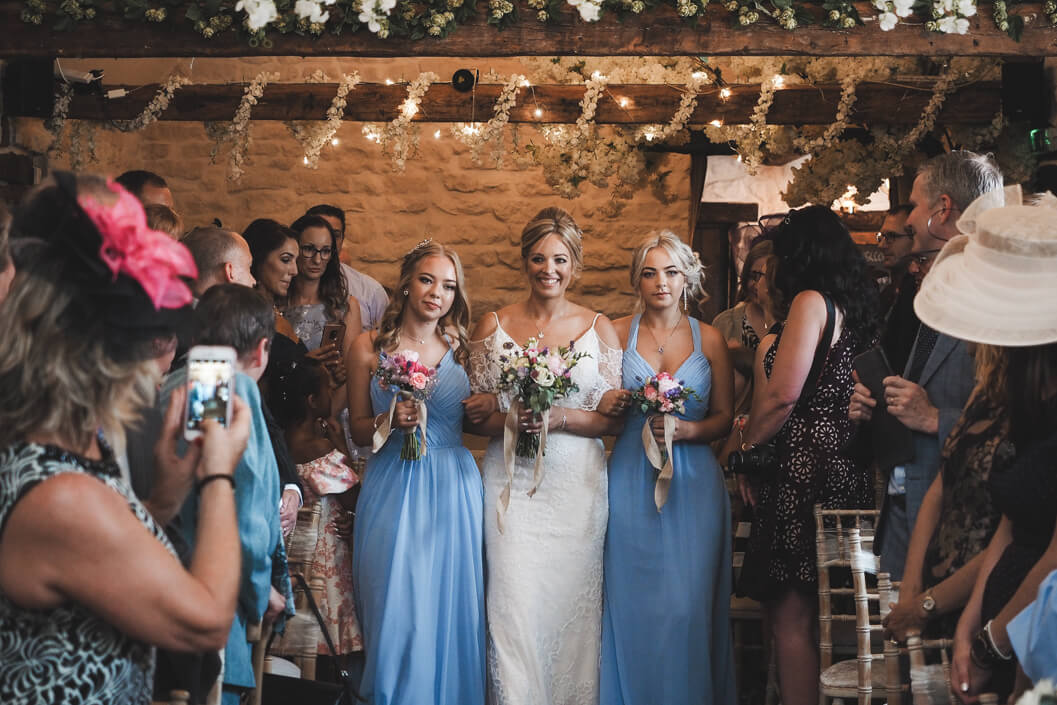 bride and bridesmaids entering the old barn at crossbutts stables for the wedding ceremony