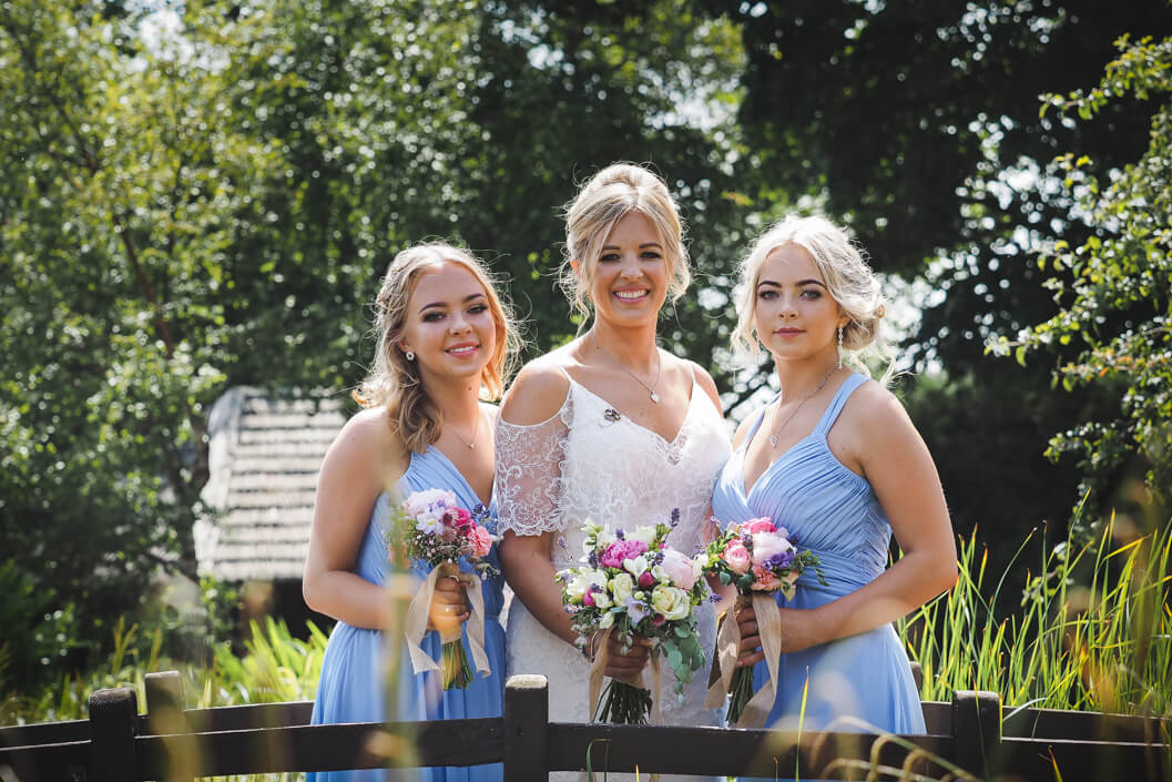 bride and bridesmaids in the gardens at crossbutts stables, whitby