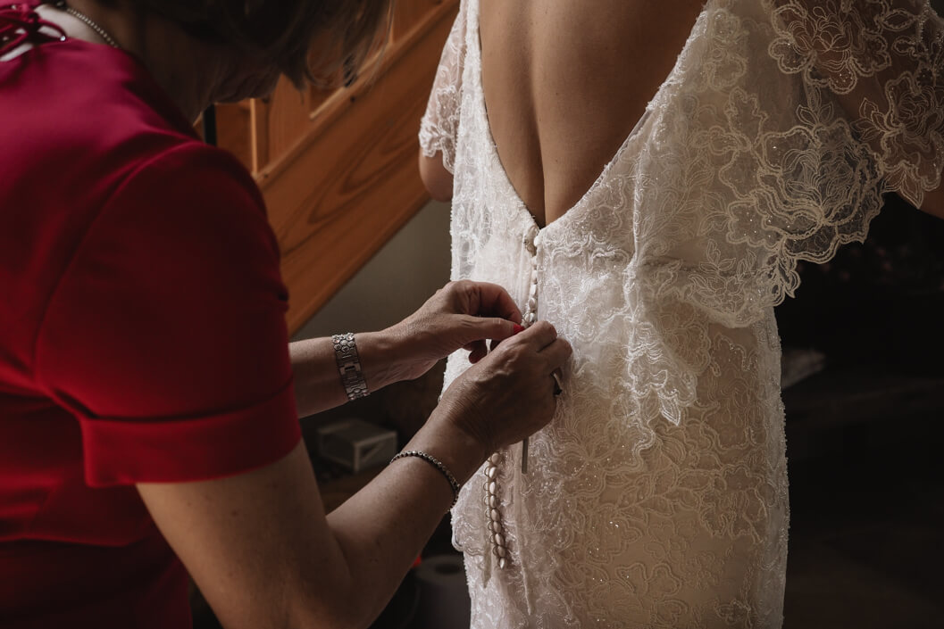 bride having the finishing touches to her dress at crossbutts stables, whitby