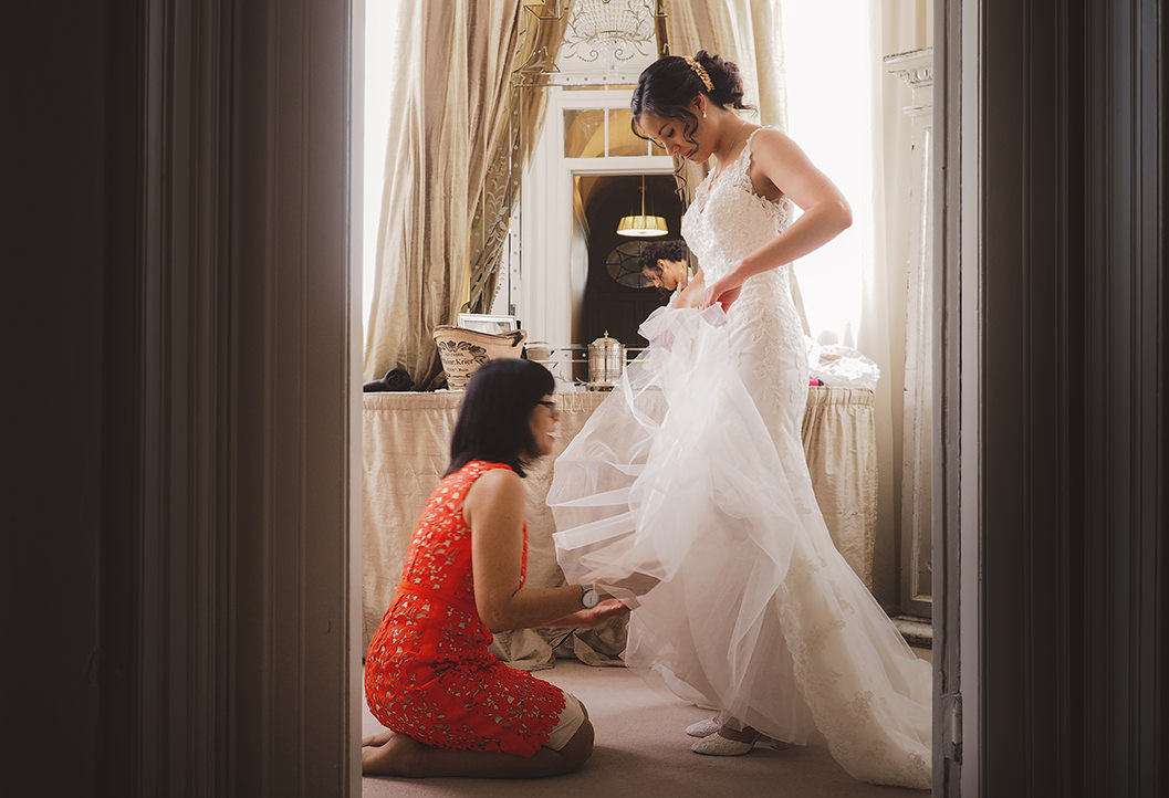 Rosie & brides mother at howsham hall with the final touches to the wedding dress