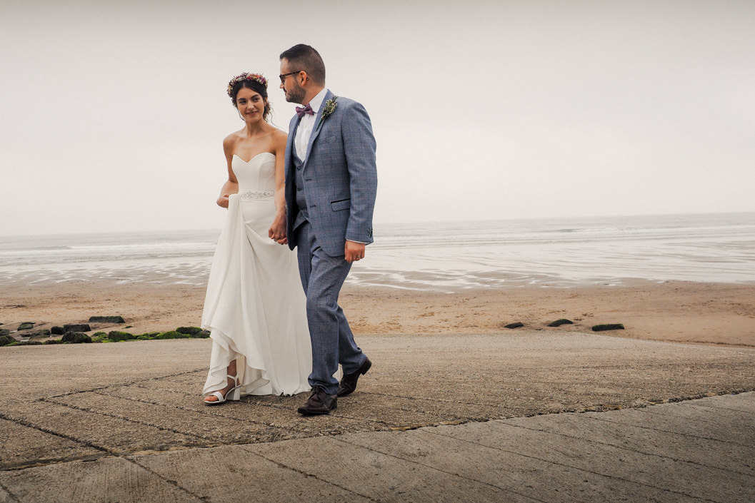 bride and groom photo leaving the beach in whitby